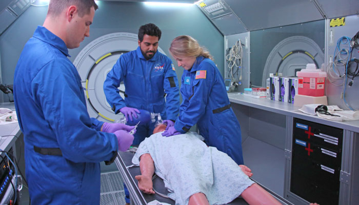 woman gives chest compression to mannequin in NASA simulator