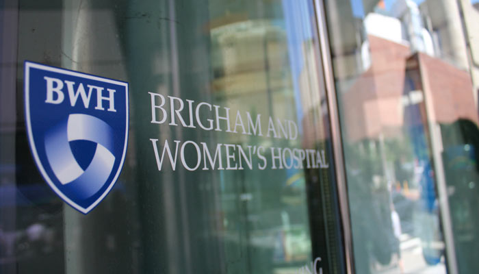 The Brigham and Women's Hospital logo shield on a window in the Longwood Medical Area, Boston, MA.